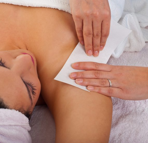 Beautician waxing armpit to a woman in a salon